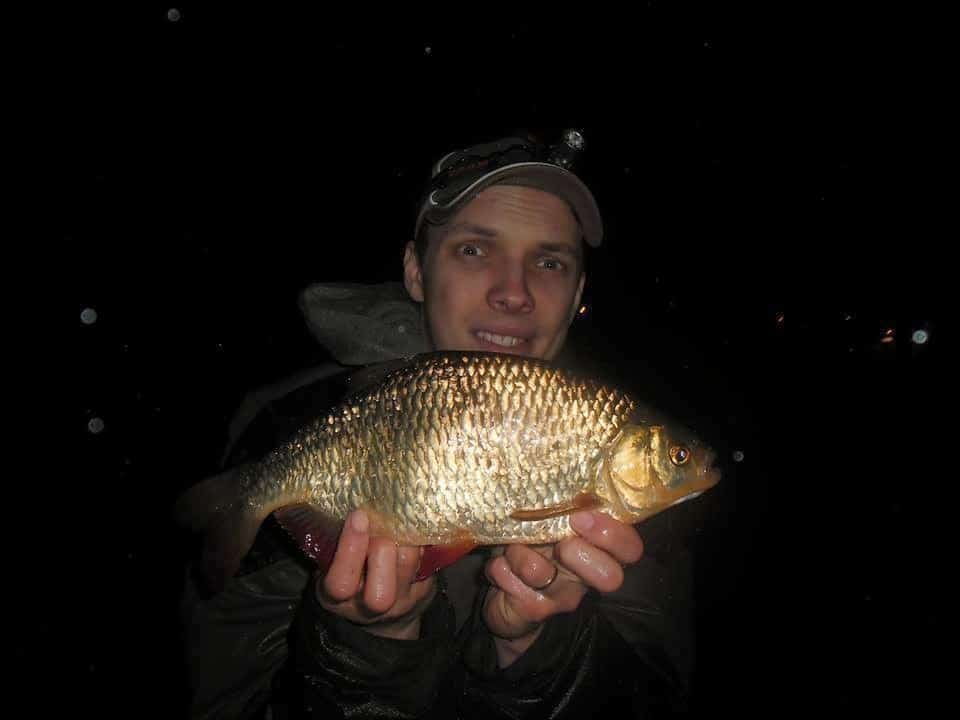 a night fisherman holding a big rudd that he has caught in the rain