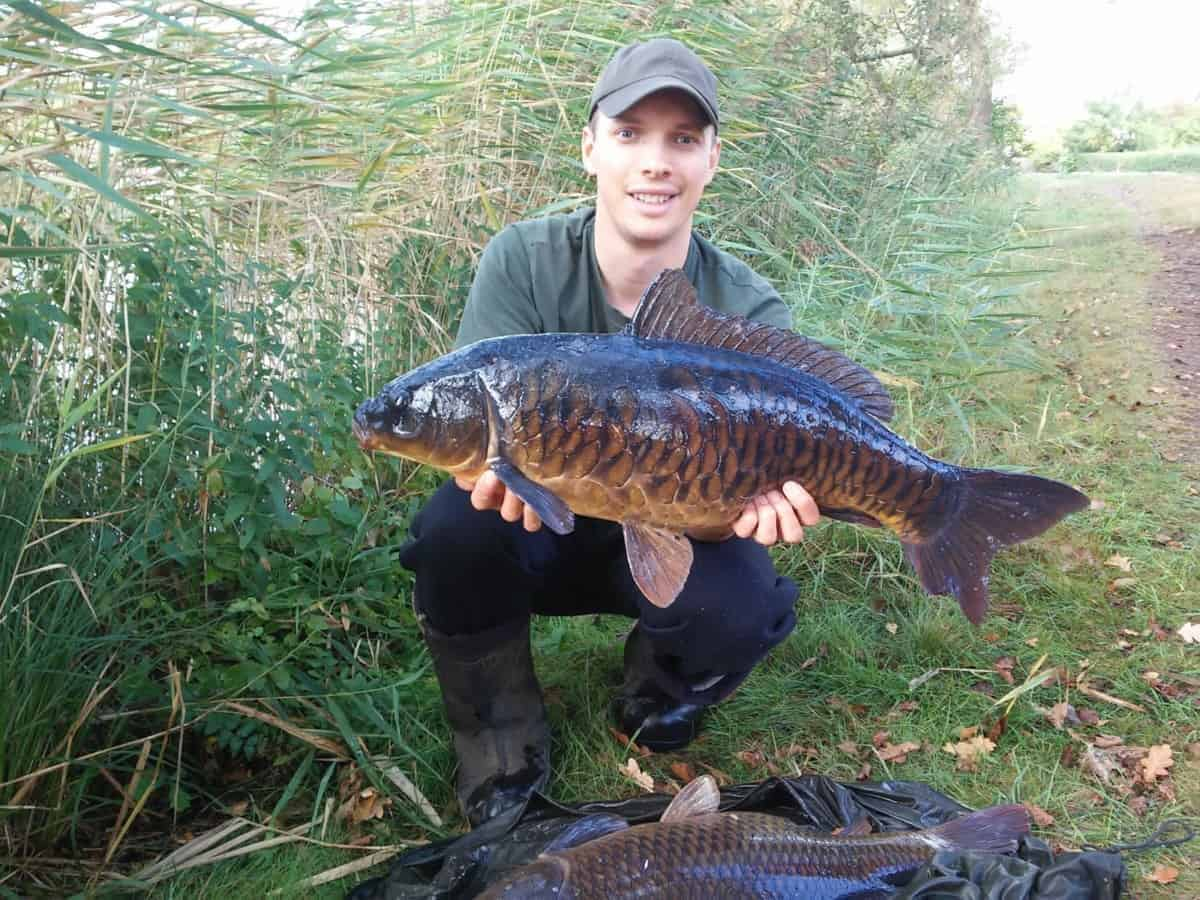 a fisherman holding a nicely looking fully scale carp