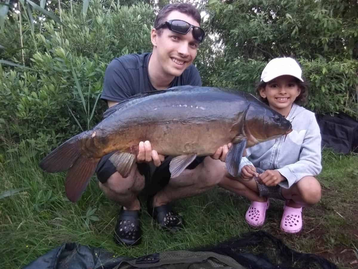 a carp angler with his little daughter holding a nice leather carp