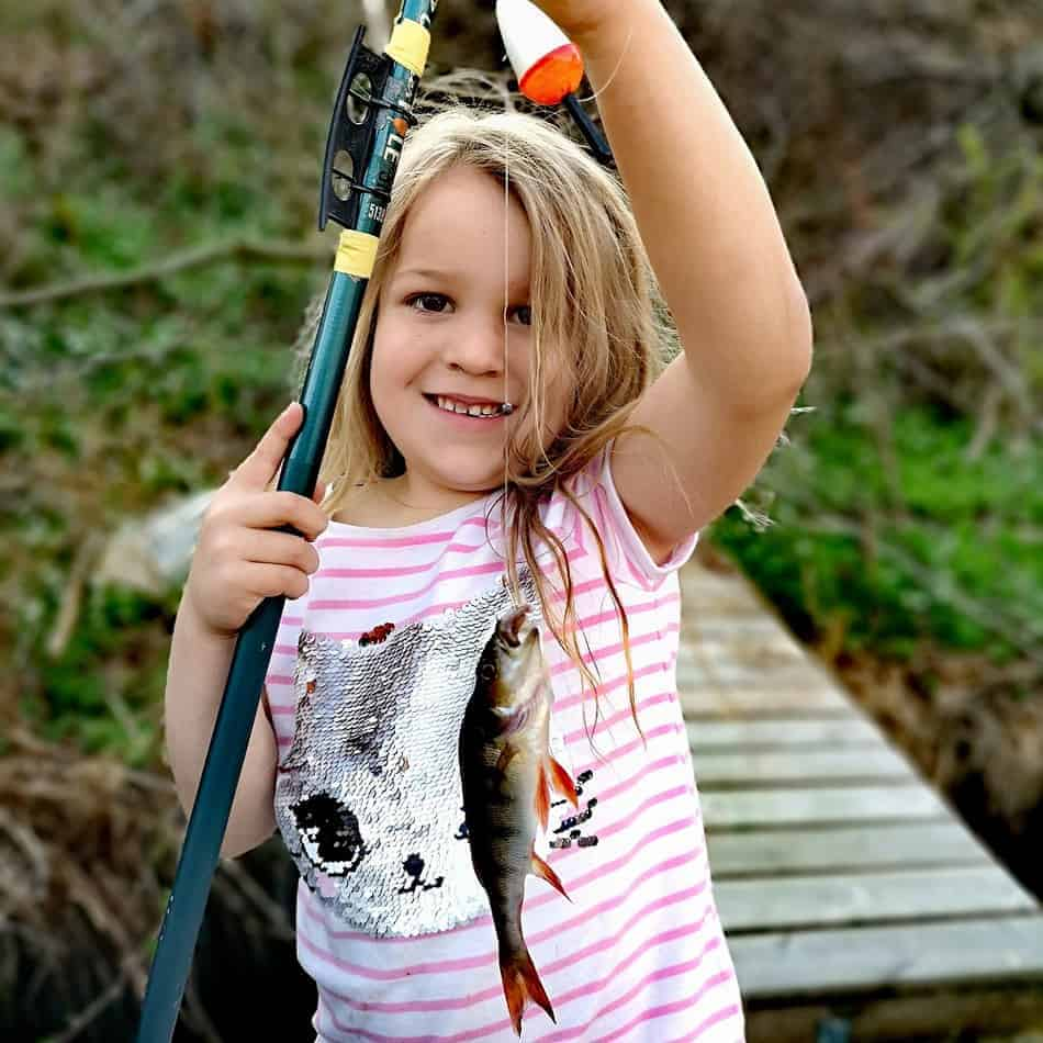 a little girl holding a fishing pole and a small perch