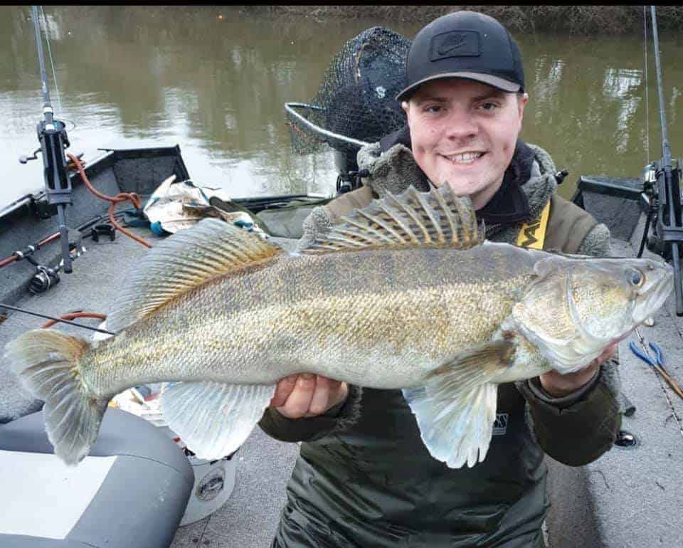 an angler holding a big zander that he has caught on a softbait using a thin wire trace suitable for zander fishing