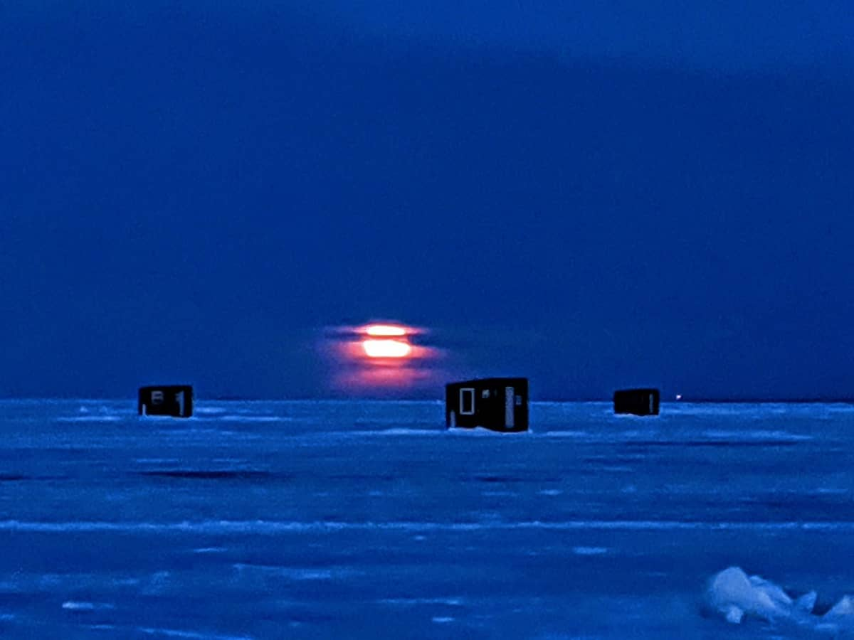 a picture of a frozen Minnesota lake by night with ice shacks on it