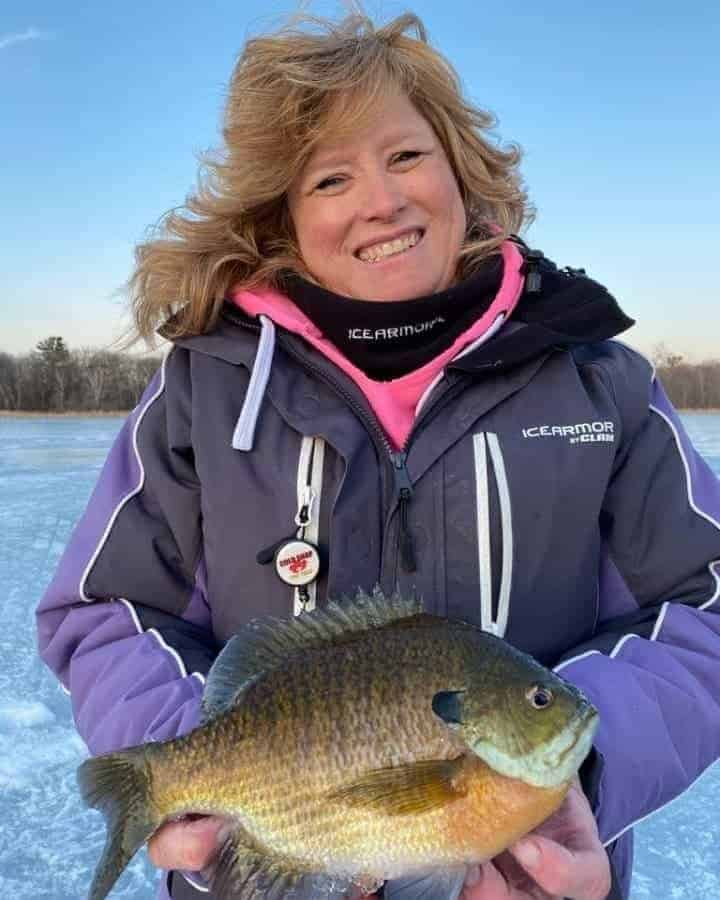 a female angler on a frozen lake in Minnesota holding a really big bluegill