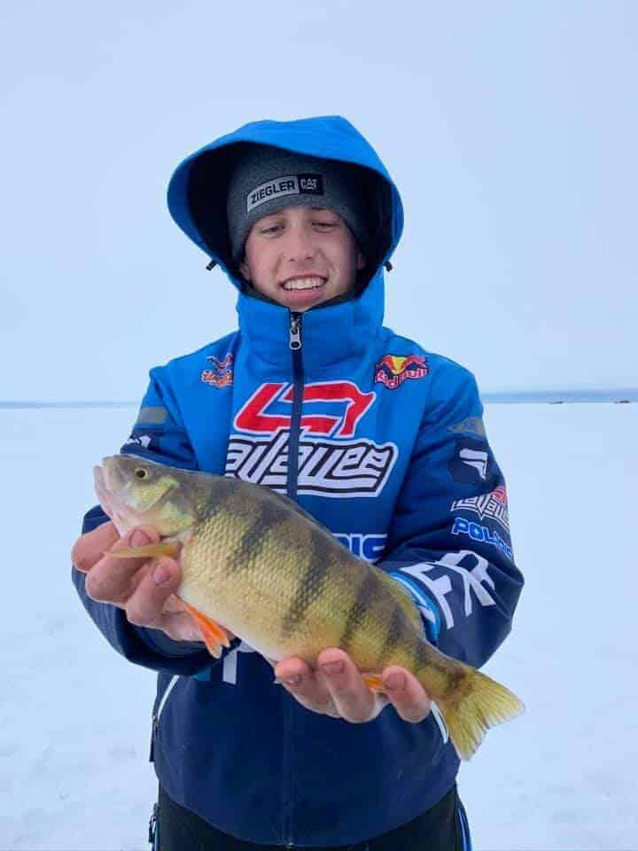 a young ice angler on a frozen Minnesota lake with a nice yellow perch