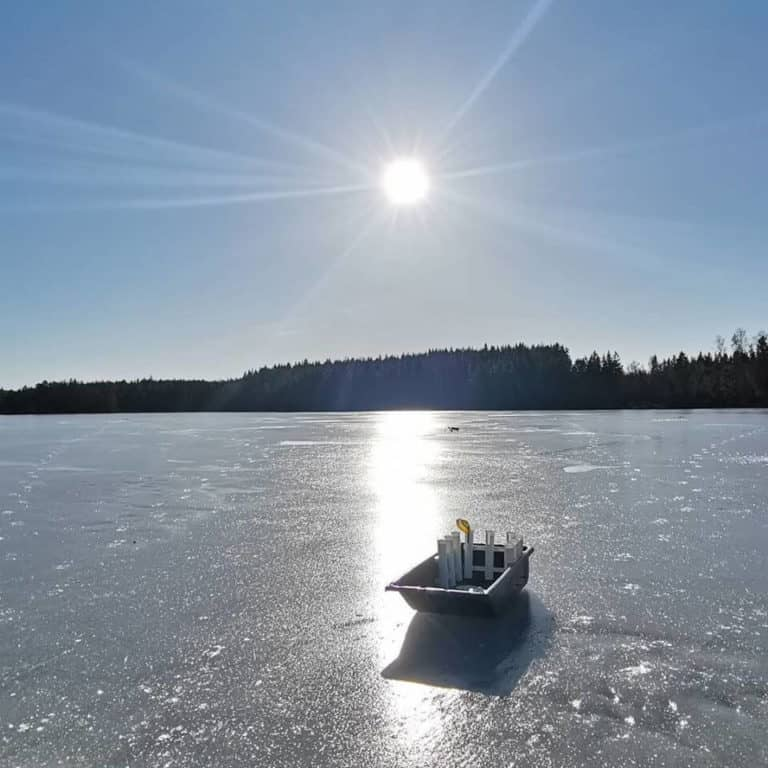 a picture of a frozen lake with an ice fishing sled with fishing gear on it