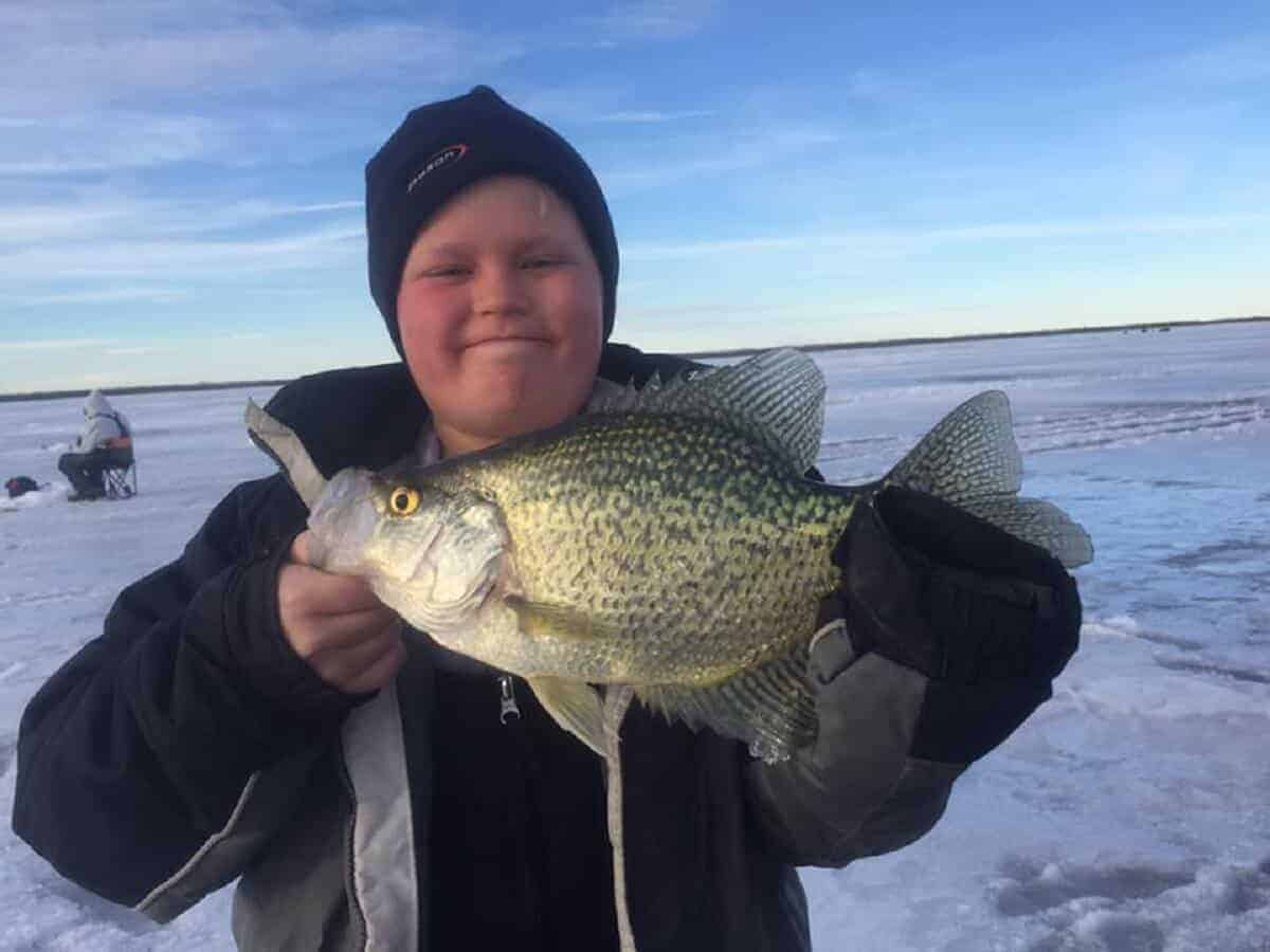 a young fisherman on a frozen Minnesota lake holding a nice crappie