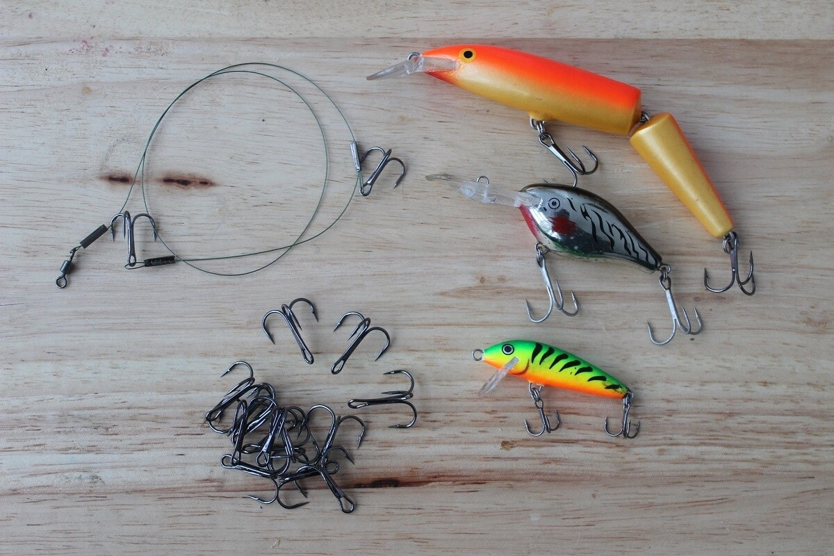 trebles hooks for lures and wire leaders for predator fishing displayed on a table together with some crankbaits and a quick strike rig.