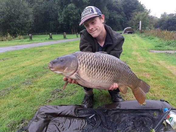 a happy carp angler holding a giant common carp over a beanie unhooking mat