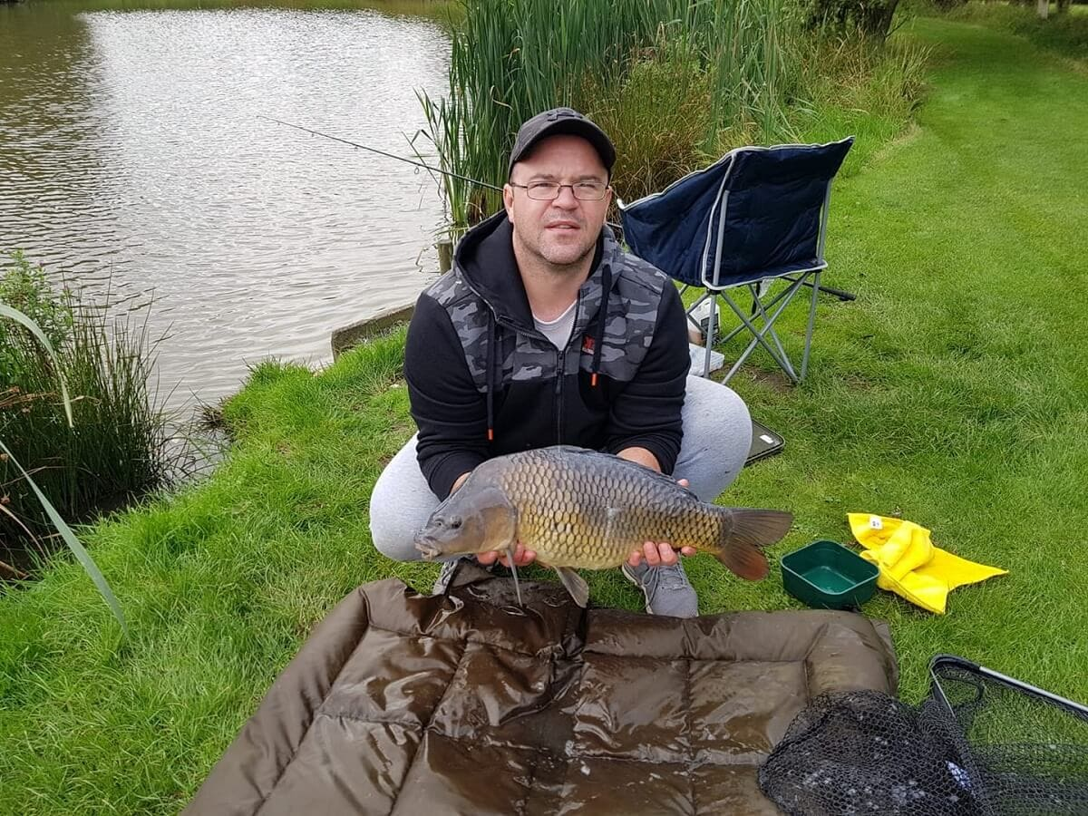 a carp angler using a beanie unhooking mat to handle a nice common carp