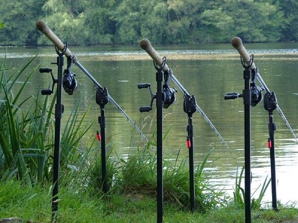 a set of three tench fishing rods on bank sticks with bite alarms and bobbins on the bank at a lake