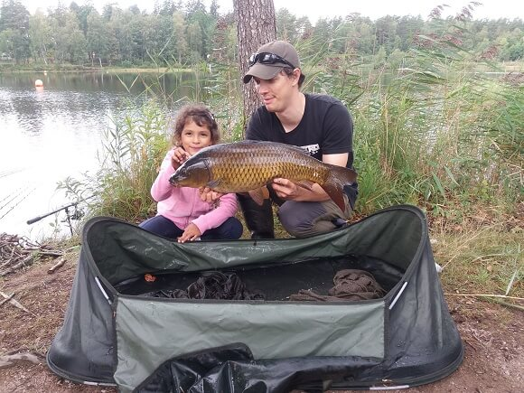 a carp angler and his daughter holding a common carp and using a carp cradle to handle the fish correctly.