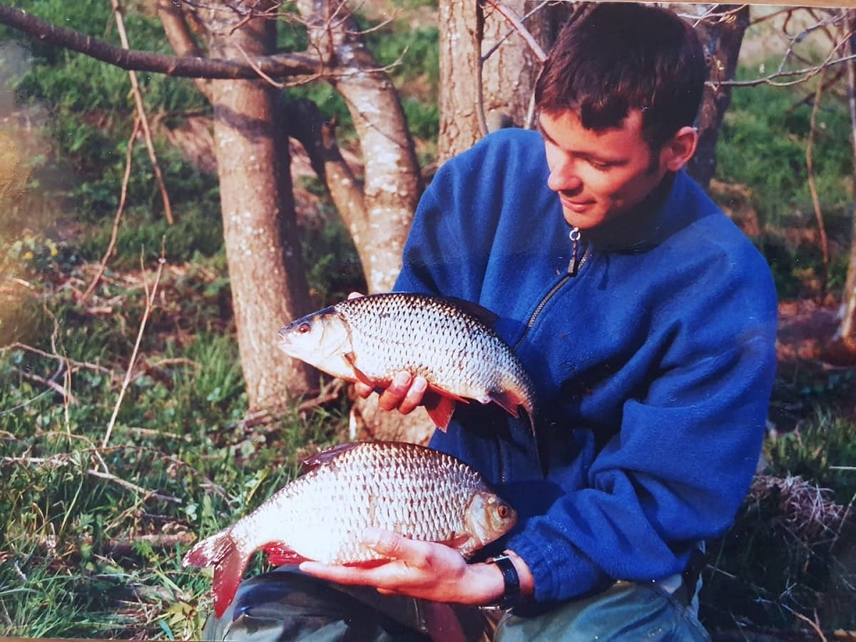 a specimen angler holding a big roach and a big rudd that he has caught on the feeder rod in a lake