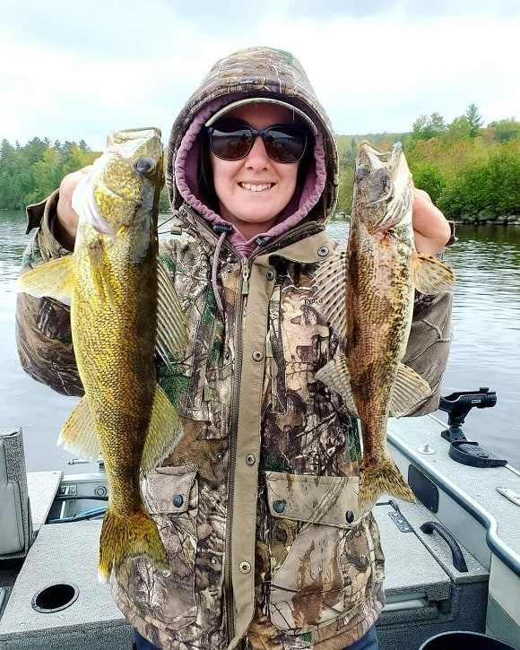 a female angler on a boat holding a walleye and a sauger that she has caught on a small crankbait