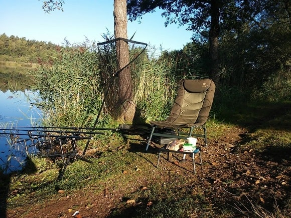 a carp fishing chair, a 42 inch landing net, and a rod pod with three carp rods on a bank