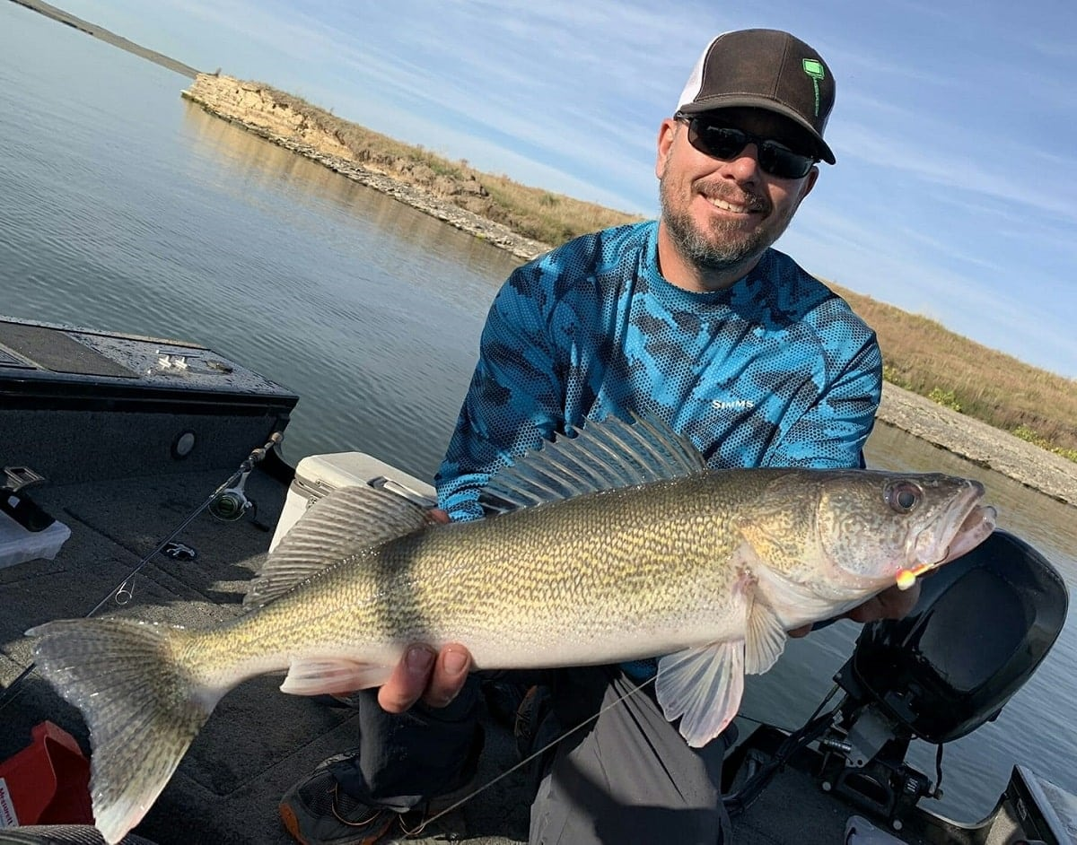 a fisherman on a boat holding a long walleye that he has caught on a fluorocarbon leader and a crankbait