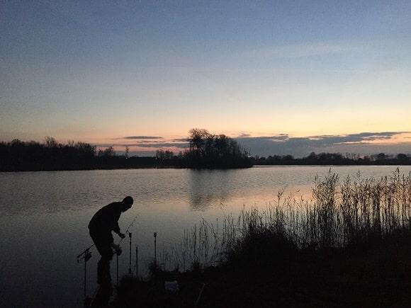 a carp angler adjusting his rods while fishing in a Swedish carp lake