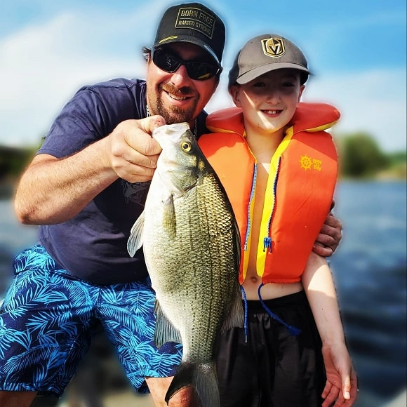 a fisherman and a young kid on a boat holding a white bass that they have caught on a small crankbait
