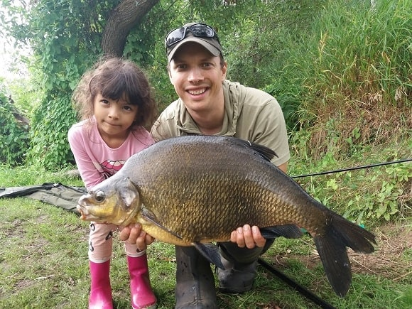 a coarse angler and his daughter with a huge common bream caught over a bed of groundbait and sweetcorn