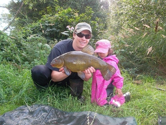 a coarse angler and his daughter with a big tench caught on the maggot feeder