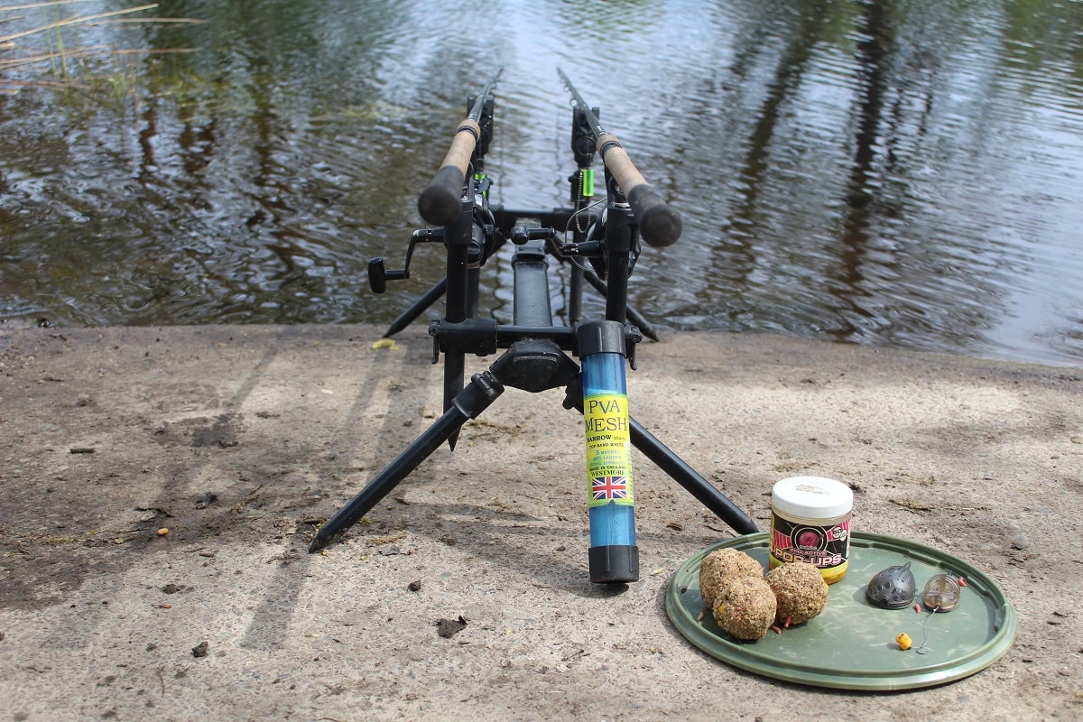 two specialist rods for tench on a rod pod with some groundbait, method feeders and pop-ups next to it