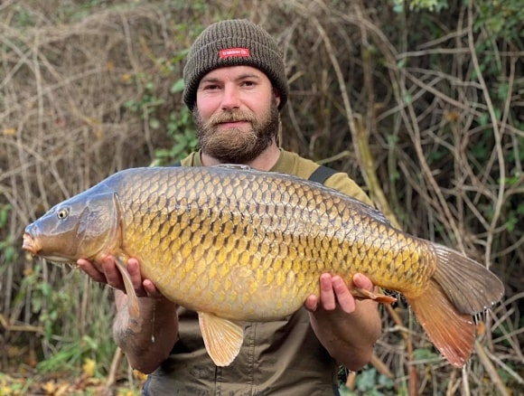 a carp angler holding a big common carp that he has caught on a boilie and pop-up