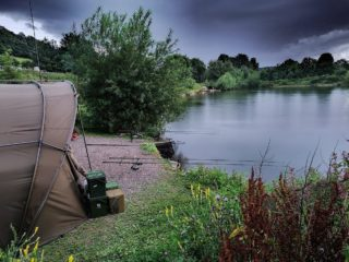 a carp swim with a bivvy and a set of rods on a small lake