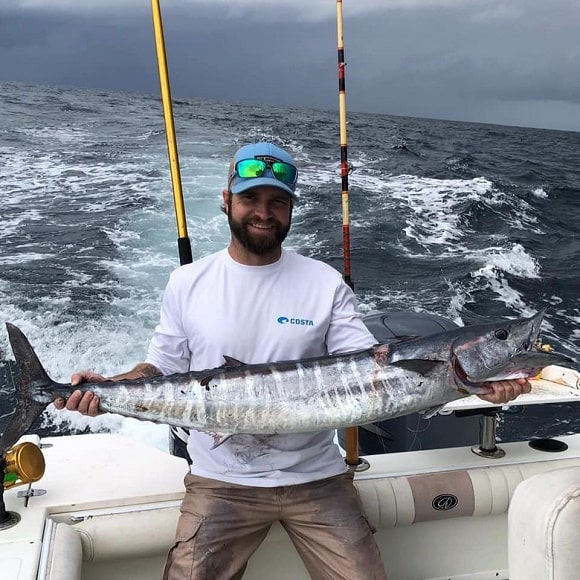 a saltwater fisherman on a boat holding a big wahoo that he has caught on a trolling wahoo lure