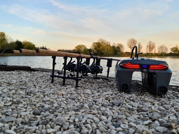 a bait boat on the bank next to a rod pod with three carp fishing rods
