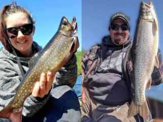 two anglers on a boat holding a beautiful brook trout and a splake