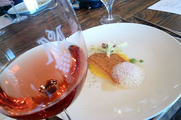 an image of a steelhead fillet on a plate next to a glass of rosé wine