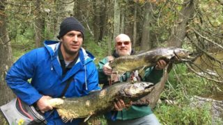 two anglers on a river bank each holding a big zombie salmon