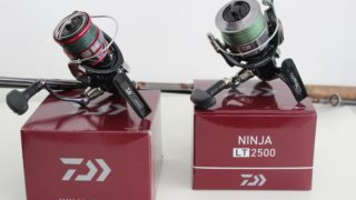 an image of two fishing reels and a fishing rod on a white table