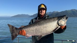 a commercial salmon fisherman in Alaska on a boat holding a giant king salmon