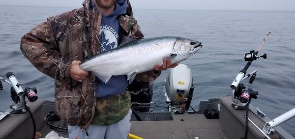 a fisherman on a boat holding a big sea run chinook salmon