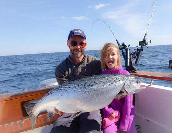 a happy angler and his daughter on a boat holding a giant Atlantic salmon