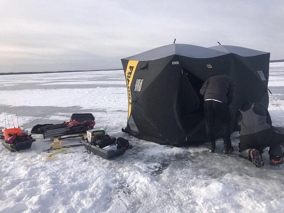 two ice anglers preparing their pop-up shelters and ice fishing equipment on lake simcoe