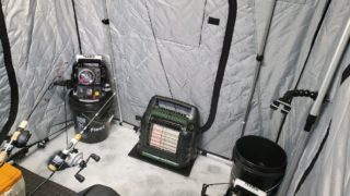 the inside of an ice fishing shack with a mr buddy heater and two portable fish finders