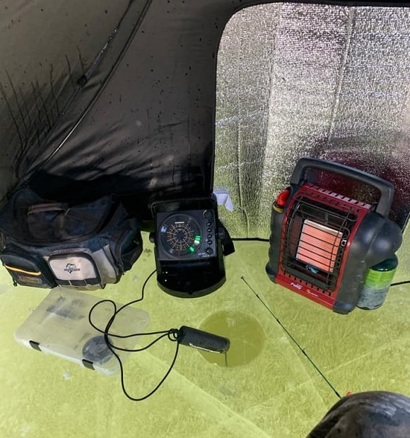 the inside of a pop-up shelter for ice fishing with a mr buddy heater on the ground