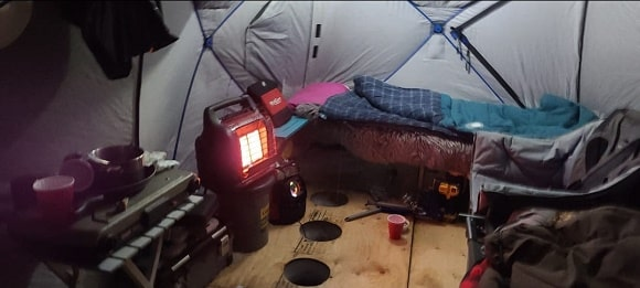 a permanent ice house with a bed and a mr heater buddy for warmth