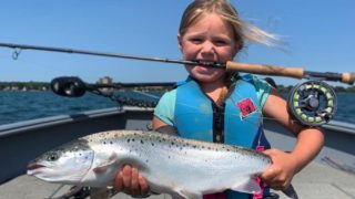 a young angler on a boat holding a big landlocked Atlantic salmon