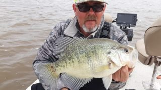 a crappie angler on his boat holding a really big stained water crappie