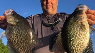 a US angler on his boat holding two big crappies