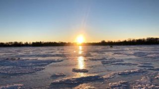 a beautiful morning on a frozen lake nipissing with a rising sun