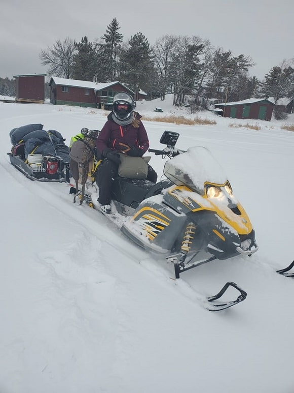 a female angler sitting on a snowmobile on lake of the woods