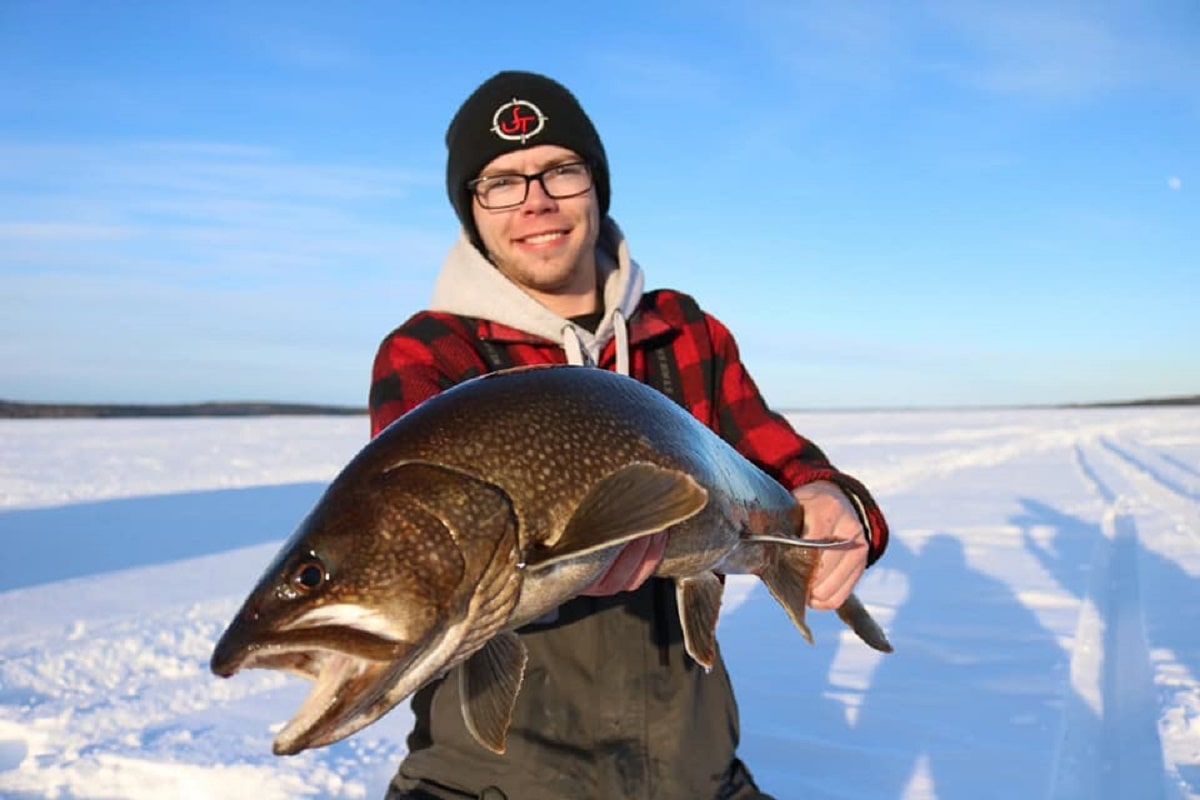 a US ice angler on a frozen lake with a nice lake trout
