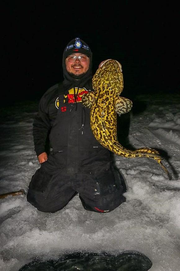 a fisherman ice fishing for burbot at night on lake nipissing