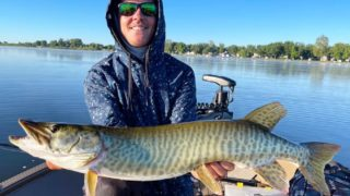 a happy angler on his boat with a beautiful clearwater muskie